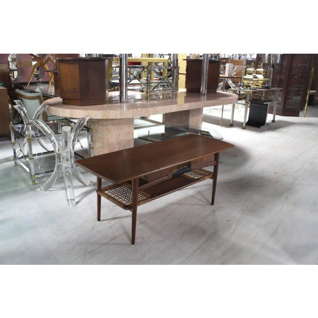 Very nice Danish modern coffee table with rattan shelf 4 drawers storage compartment and rolled edges. Forged brass pulls...