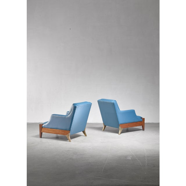 A pair of lounge chairs by Italian designer Melchiorre Bega. The chairs are made of walnut wood with brass back legs and a...