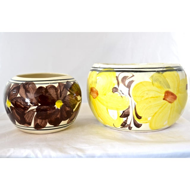 """Pair of hand-painted floral motif planters in vibrant yellow, brown and black on cream ceramic. Marked """"Mexico.""""..."""