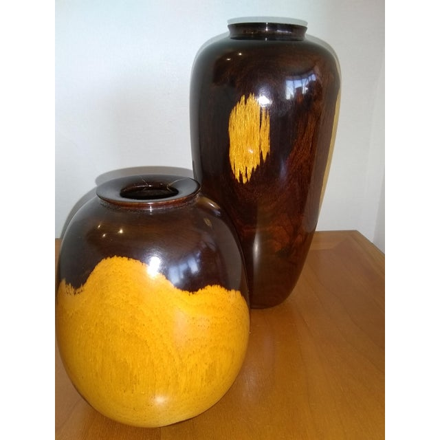 "This elegant pair of black and tan vases is made of beautifully crafted turned wood. The taller vase measures 8.75""(h) x..."