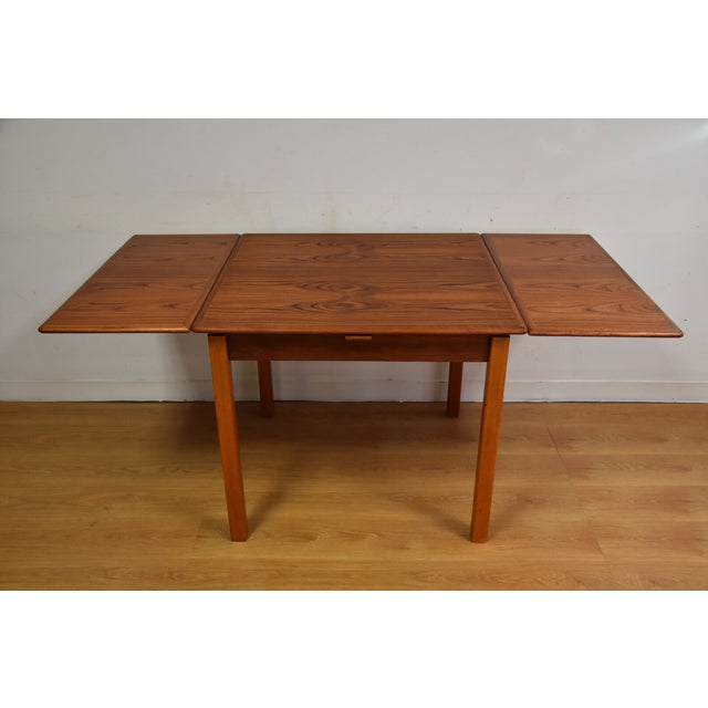 A mid-century modern teak dining table with two draw leafs that hide away under the top. Made in Denmark. Table expands to...