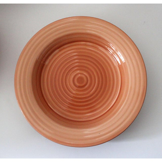 This is a rare set of tangerine-colored HausenWare plates. The set contains 1 large serving bowl, 6 dinner plates, 4 salad...