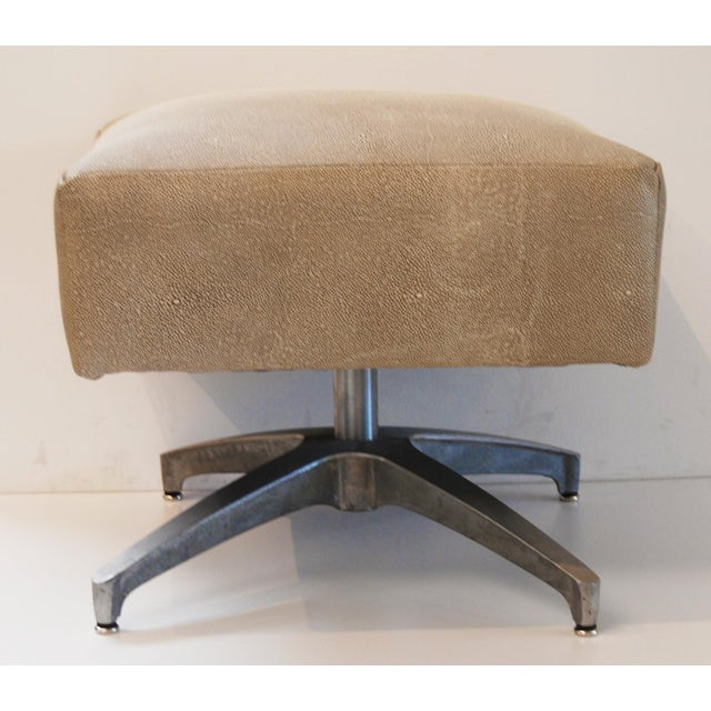 Add a little bit of lift with this modern, Eames-inspired ottoman featuring a neutral upholstery made to mimic shagreen....