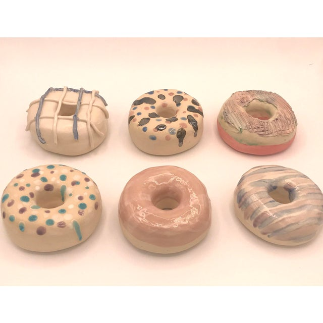 Handmade stoneware clay donuts. Each donut I form of a slab (flat sheet of clay) and build it hollow. I then hand sculpt...