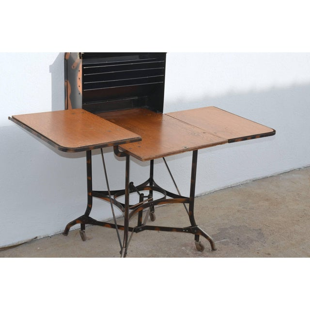 Early Industrial rolling desk by Toledo. Great for a laptop desk. A lever picks up the desk on wheels for easy moving and...