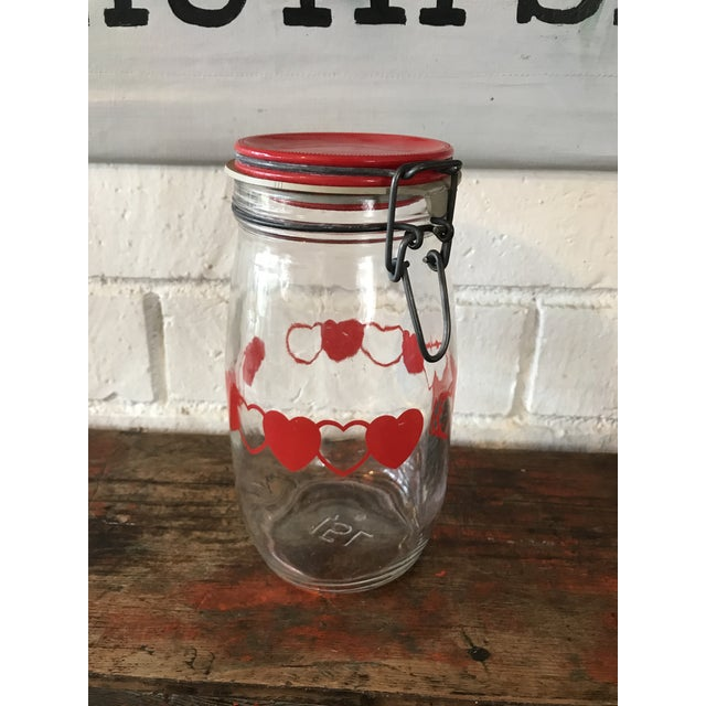 Vintage glass jar or canister with red hearts and metal baled lid in red. In excellent condition. The rubber seal is...