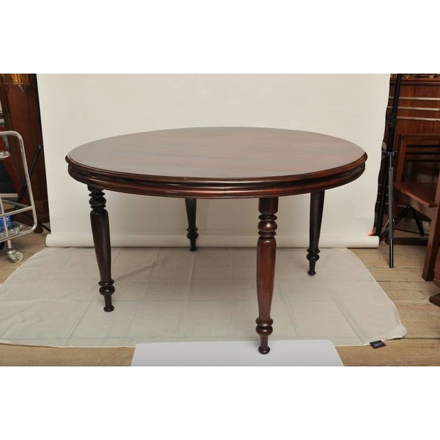 This is an elegant and rare British Campaign solid rosewood dining table. Reeded edges and turned legs, which unscrew from...