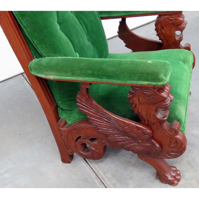 Early 20th Century Renaissance style carved winged griffin chair upholstered in green velvet fabric with button tufted back.
