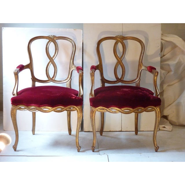 French early 20th Century well made, sturdy, comfortable armchairs, carved giltwood with scroll feet, set back arms. The...