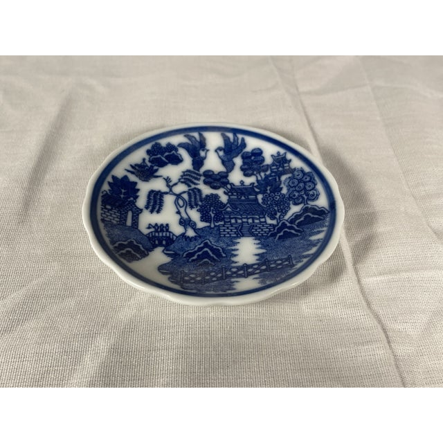 This stunning miniature saucer is done in the traditional blue willow pattern and has a unique scalloped edge. It has a...
