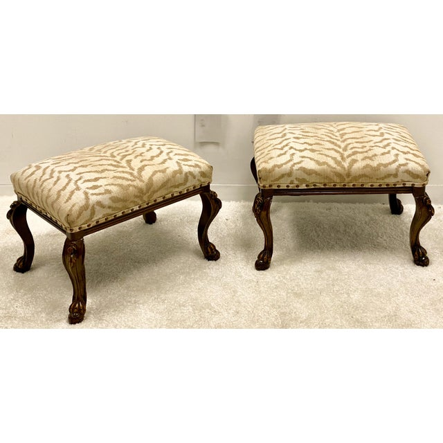 This is a vintage pair of carved walnut ottomans with French styling. The ivory tiger fabric feels like a chenille or...