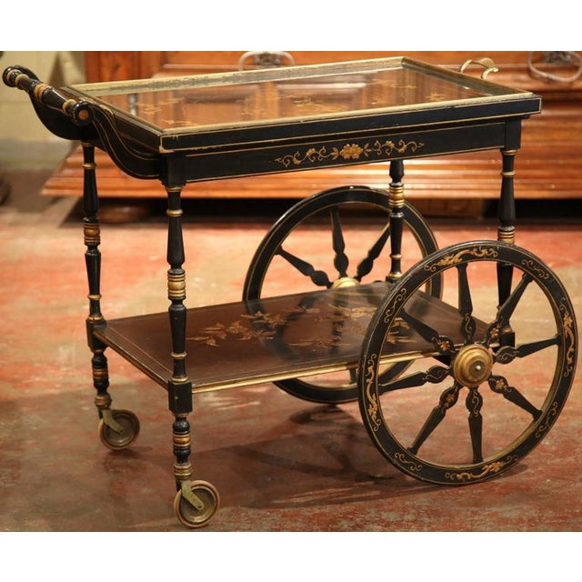 This fine wooden tea cart was created in France, circa 1920.The cart is on wheels and is painted black with chinoiserie...