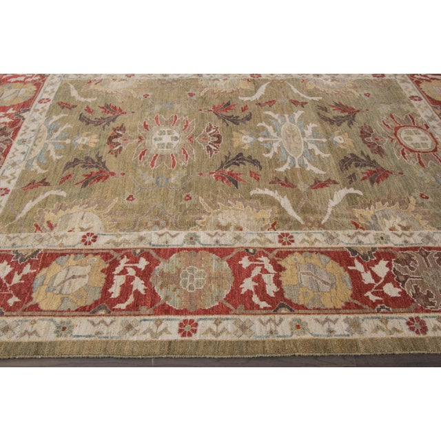 A hand-knotted Sultanabad rug with a floral design on a green field. Accents of red, ivory and brown throughout the piece.