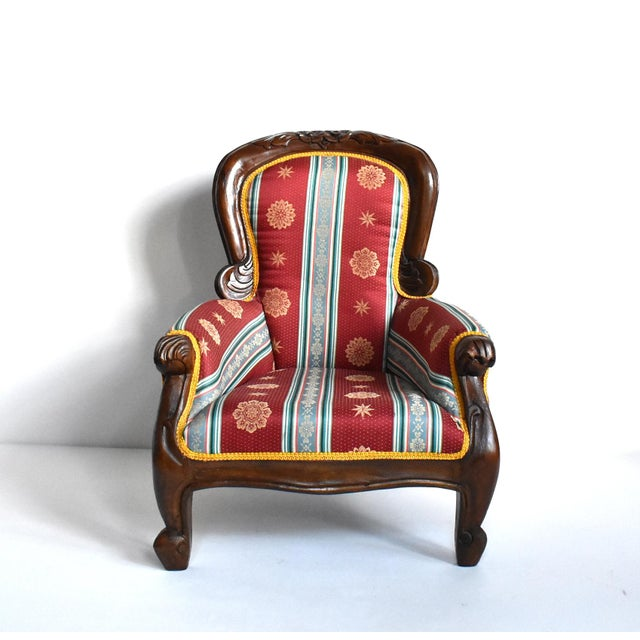 "An antique children's chair in the classic 19th-century Victorian ""grandfather chair"" style, with hand-carved details on..."