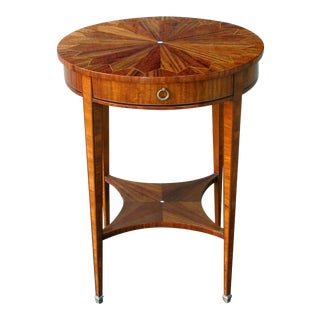A well-crafted and richly-grained English Edwardian matchbook-veneered circular single-drawer side table