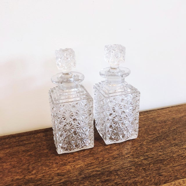 """Set of 2 pressed glass liquor decanters. Would also serve as beautiful bath oil and salt decanters. 2.75"""" wide x 7.25"""" tall"""