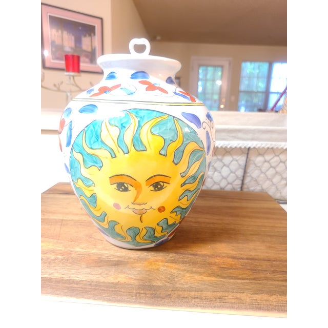 Beautiful larger ginger jar is handpainted with lovely sun pattern on front and back. Blue and red flowers enhance both...