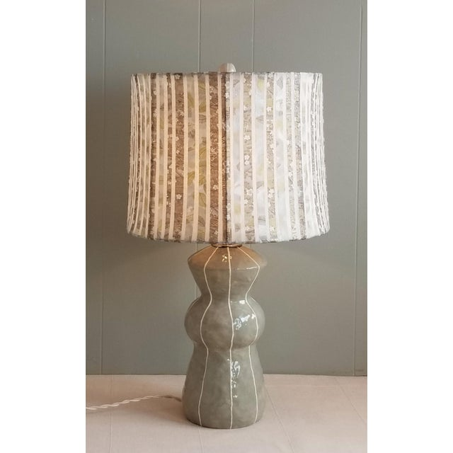 Medium size gray ceramic table lamp has an organic geometric shape and is topped with handmade rice paper collage shade...