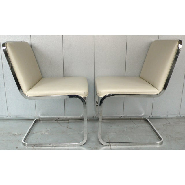 Set of four cantilevered chairs in polished chrome with original faux lizard naugahyde upholstery. Made by Brueton, c....