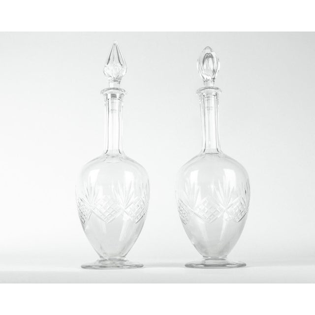 Vintage pair of exquisite cut crystal French liqueur decanters. Each decanter features a footed base, voluptuous curves...