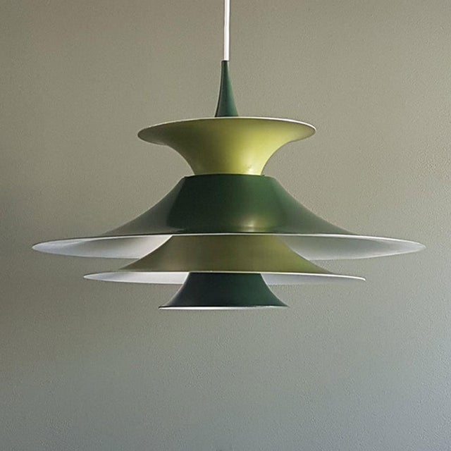 A beautiful and rare pendant lamp design by Erik Balslev for Fog & Mørup in the 1960s, in its original light and darker...