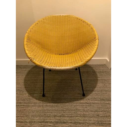 This is a super-fun vintage mid-century atomic style basket chair in a very sunny yellow with a white weave and black...