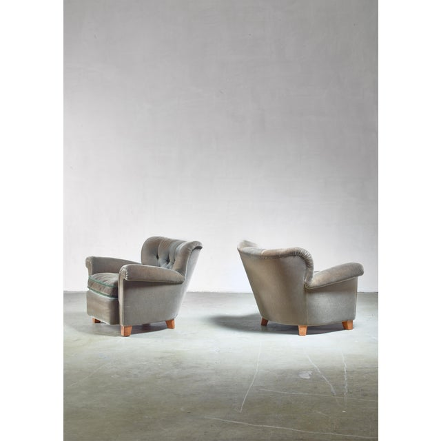 A pair of lounge chairs attributed to Carl-Johan Boman for Oy Boman, Finland. The chairs stand on wooden legs and have the...