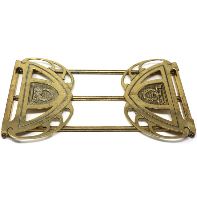 A vintage brass art deco book rack, with articulated ends that fold flat. Each end has an embossed wreath and ribbon...