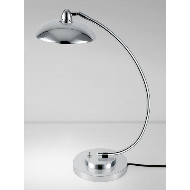 A polished chrome desk light with a shallow directional head. This light has an opal acrylic diffuser which gives warm LED...