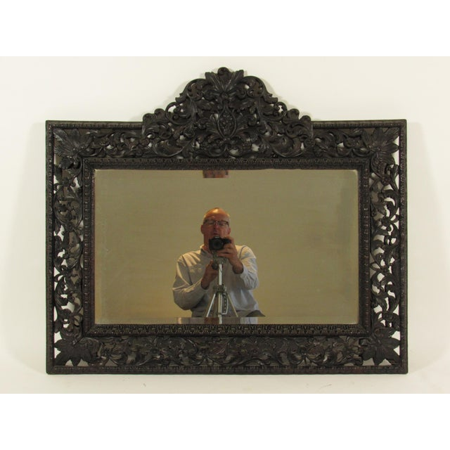 A late 19th century English Rococo-Style dark stained, and pierced carved walnut mirror with original bevel glass.