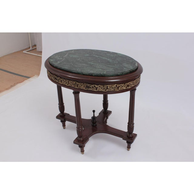 Green Marble Top Accent Tea Table with decorative brass work on Apron. Have some veneer peeled off on the base.