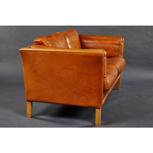 A Scandinavian settee in a rich and beautifully worn original leather. Please also see our matching sofa.
