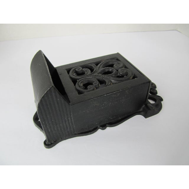 Beautiful vintage black iron match safe. This piece is perfect in a kitchen, mounted next to a fireplace, or even near...