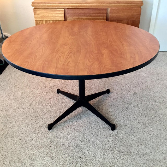 We have a wonderful Eames for Herman Miller authentic Dining Table. The top is an engineered walnut grain with a black...