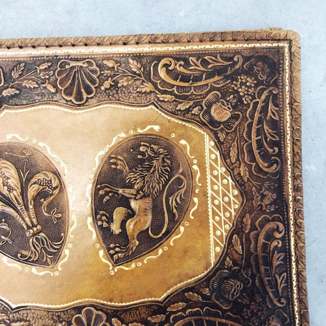 Antique tooled leather bound memory book with fleur-de-lis and lion motifs on the cover. The interior is silk lined and...