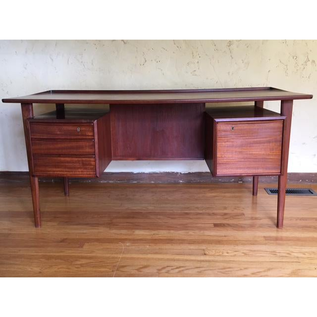 Beautifully restored mid-century Danish teak desk with floating top. Large file drawer on right and three drawers on left,...