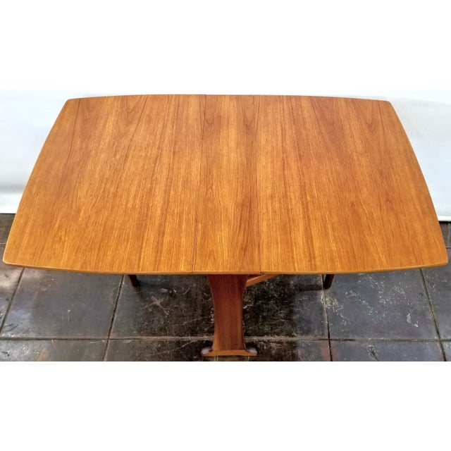 Vintage late-1960s to early-1970s gate-leg drop-leaf table by Legate Furniture of Glasgow, Scotland. The shaped table top...