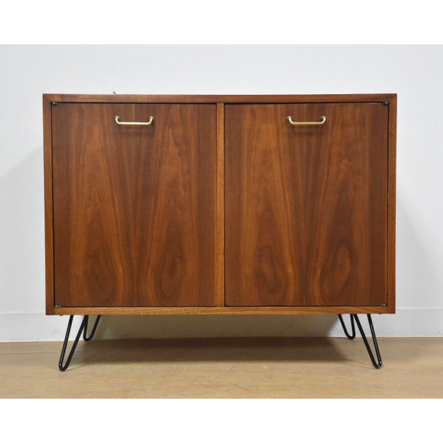 A mid century modern walnut bar cabinet designed by Merton Gershun for American of Martinsville. This bar has two doors...