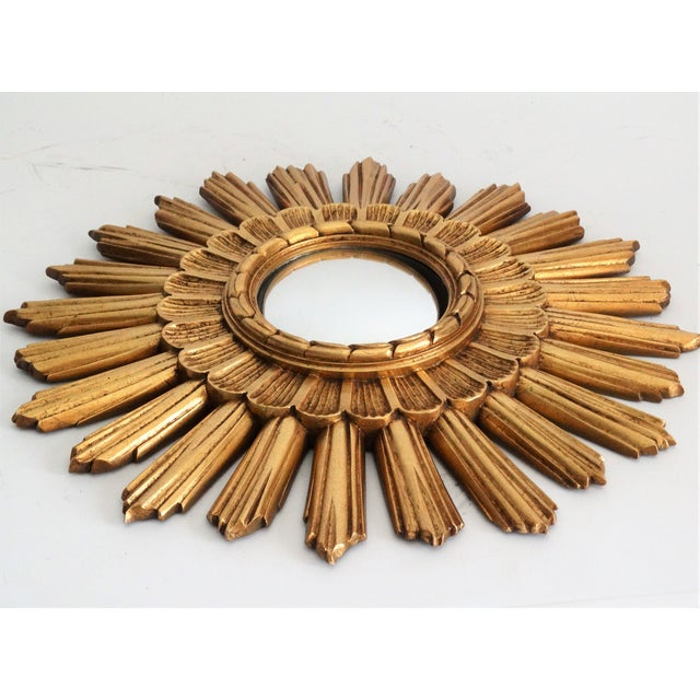 Mid Century Continental Belgian sunburst convex mirror with a gilded finish. Features a carved stepped decorative...