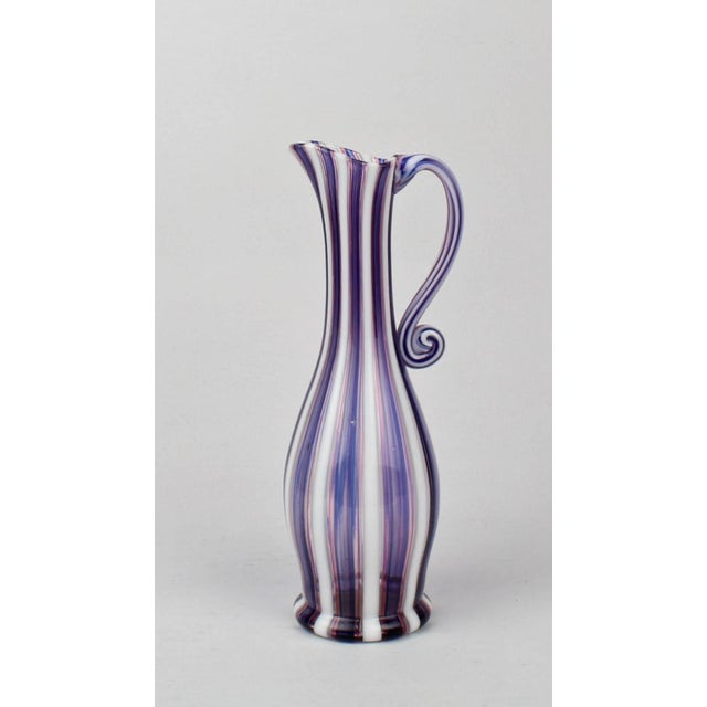 A fine Venetian pink (or red), white and blue a canne glass ewer or pitcher. Likely by Salviati. With an applied, S scroll...