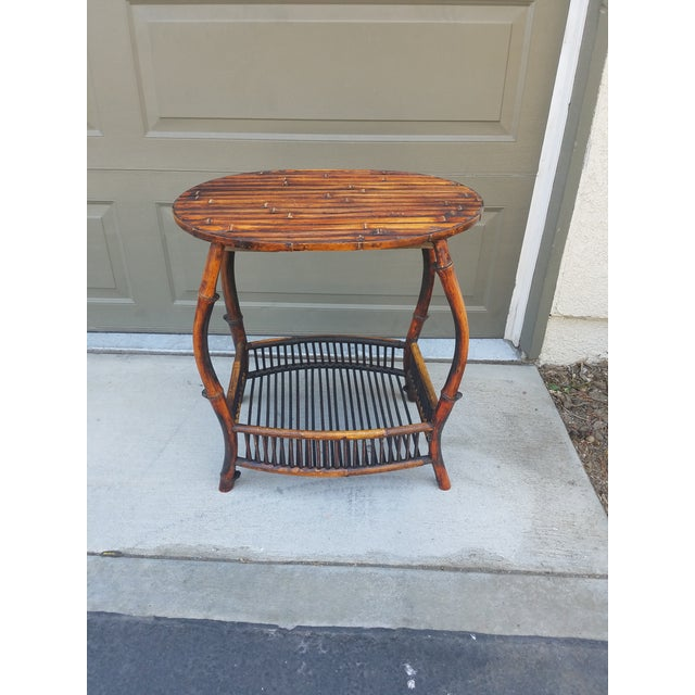 Beautiful antique oval tortoise shell finish bamboo side table. Has a bottom storage shelf. Very pretty addition to ant...