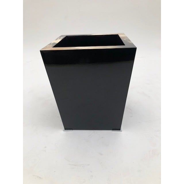 Black lacquer and buffalo horn waste paper basket on chrome feet.