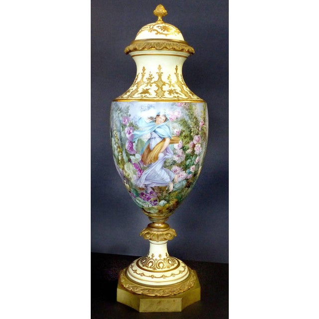 Offered is a fine Sevres hand-painted covered urn signed L. Pater. This gilt bronze mounted covered porcelain urn in three...