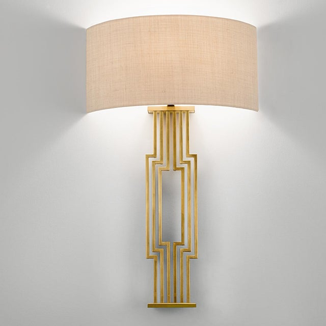 A brushed brass wall light made of a geometric pattern with a linen shade. Certification: IP20. Bulb: 1 x E27 7W LED 2700K