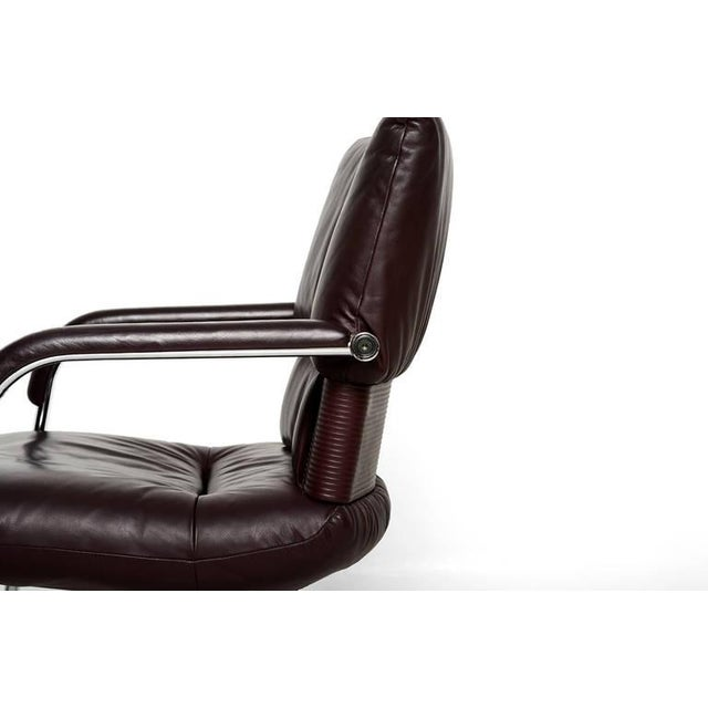 A pair of Imago office armchairs designed by Mario Bellini for Vitra. Chrome-plated steel frame with burgundy leather....