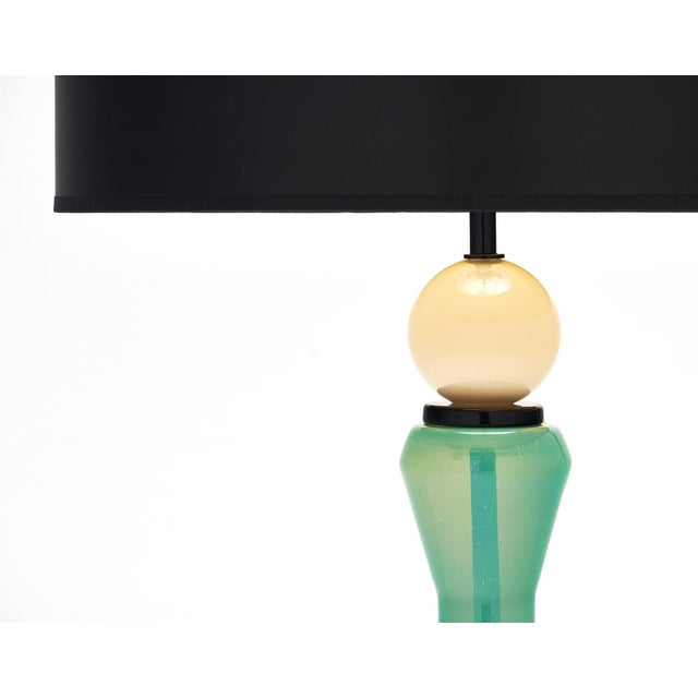 Unique pair of aqua and white Murano lamps. The hand-blown vintage glass pieces are supported by a black glass base. These...