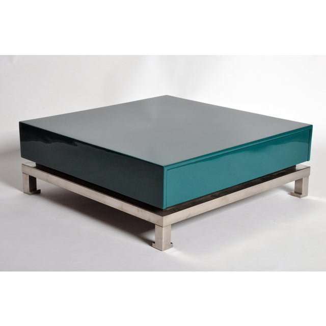 These glamorous low tables have pullout drawers hidden in their glossy teal lacquered bodies and are raised on hoofed feet.