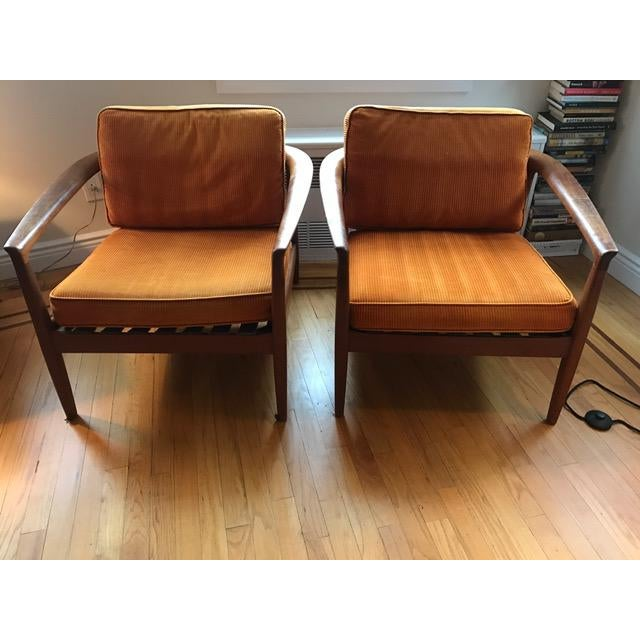 "Pair of Danish chairs marked ""DUX"" on the bottom and ""Made in Denmark."" They have a rounded barrel back and warm tone to..."