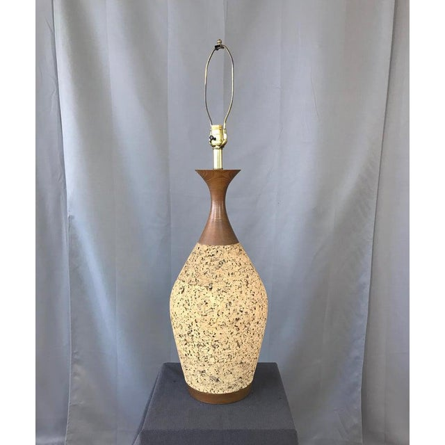 Monumental 1970s cork table lamp. Curvy walnut stain neck, and base, with a huge cork body in-between. With its original...