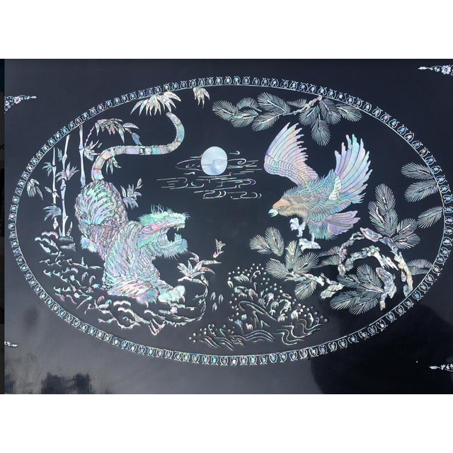 Oriental Mother of Pearl Lacquered table with claw feet. Moonlight battle between tiger and hawk is featured - it is a...
